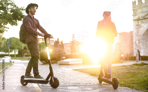 Fototapeta Modern couple using electric scooter in city park - Milenial students riding new ecological mean of transport - Green eco energy concept with zero emission -Bright warm filter with sunshine halo obraz