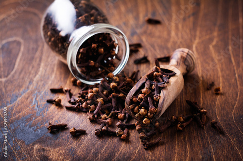 Fototapeta Cloves. Dry seasoning for cooking and drinks on a simple old wooden background. Selective focus obraz
