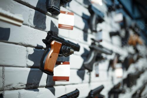 Photo Handguns on showcase in gun shop closeup, nobody