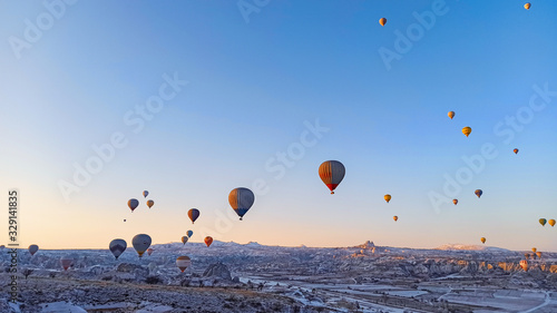 Fototapety, obrazy: Colorful hot air balloons flying over the valley with fairy chimneys in winter season. Lots of Hot air balloons at the sunrise sky landscape in Cappadocia, Turkey