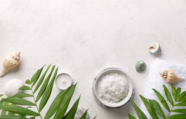 Fototapeta na wymiar spa border with natural sea salt in a bowl, candles, shells and green palm leaves on a white stone background. Relaxation and zen like concept. top view, place for text.