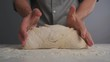 A male baker in a shirt kneads and forms the dough. Male hands with the dough. Close-up.