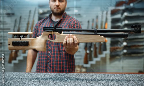 Fotografie, Obraz Male person shows pneumatic rifle in gun shop