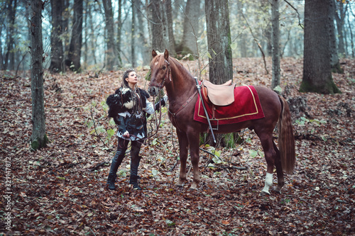 Warrior woman with her brown horse into the woods - Beautiful scandinavian vikin Canvas Print