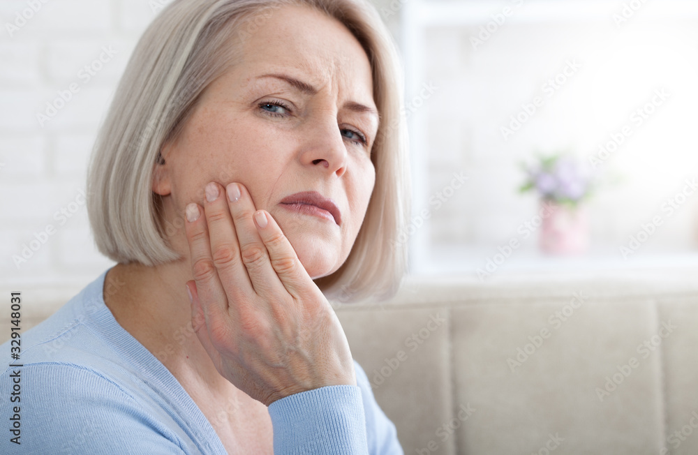Fototapeta Teeth problem. Woman feeling tooth pain. Closeup of beautiful middle-aged suffering from strong toothache. Attractive female feeling painful toothache. Dental health and care concept. High resolution.