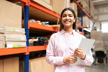 Happy Young Latin Worker With List Working At Factory