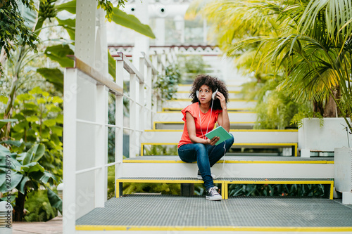 Photo Beautiful latin woman with afro hair listening to music with her tablet with her headphones in a bright greenhouse