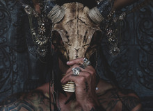 Tattooed Masked Skull Ethnic Pagan Shaman Sit On Stage An Ancient Temple.