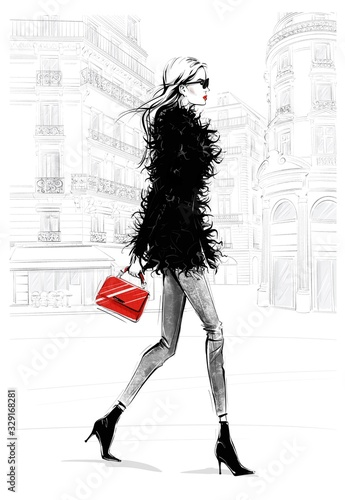 Hand drawn beautiful young woman with bag. Fashion look. Stylish girl walking with Paris street background. Woman in black feather jacket. Sketch. Fashion illustration. Wall mural