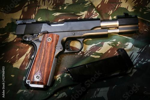 Pistola de airsoft com ferrolho deslizado em fundo camuflado Wallpaper Mural