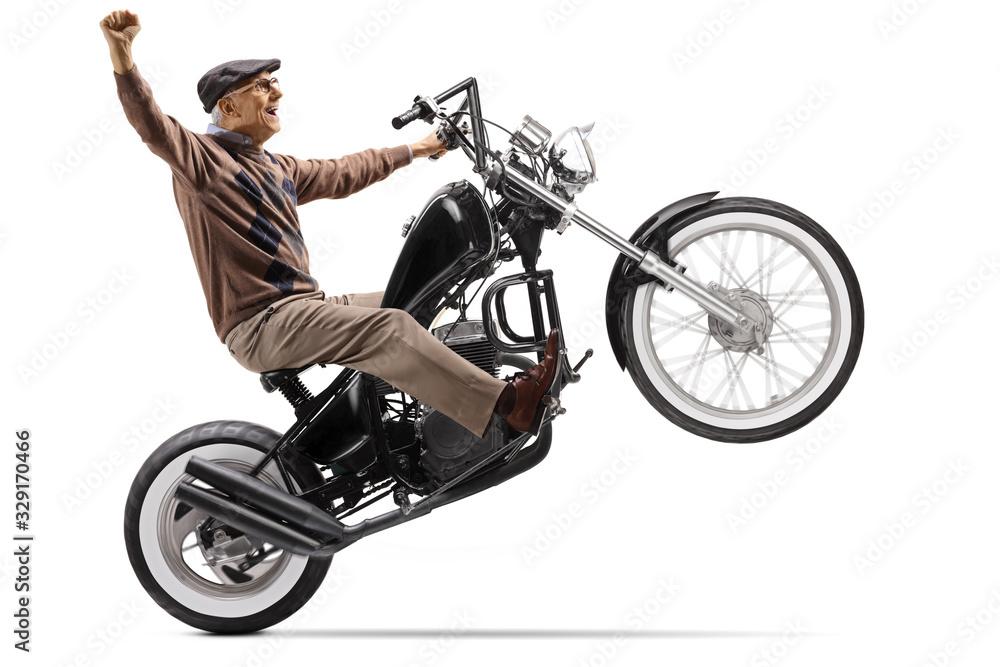 Fototapeta Senior man lifting a motorbike on one wheel and gesturing happiness