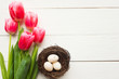 Quail eggs in the nest and tulips, top view. Easter concept