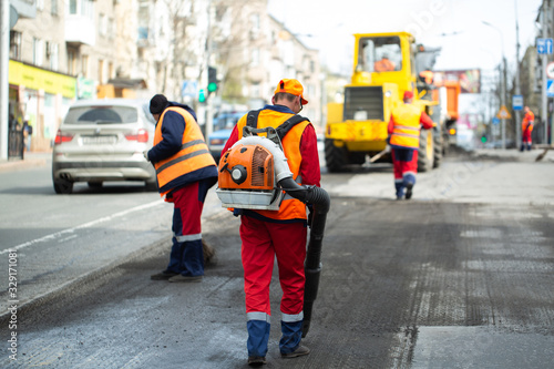 Photo Worker with leaf-blower, cleaning out the dust for better asphalt adhesion, duri