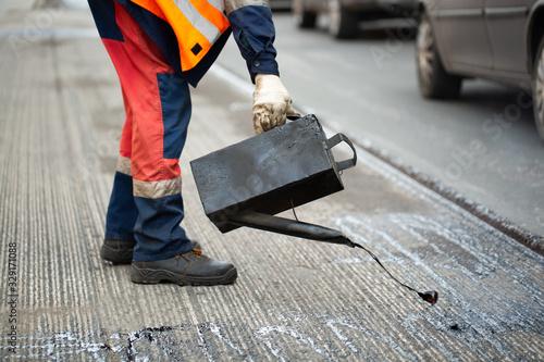 A worker pours liquid asphalt, molten bitumen from a bucket of resin Canvas Print