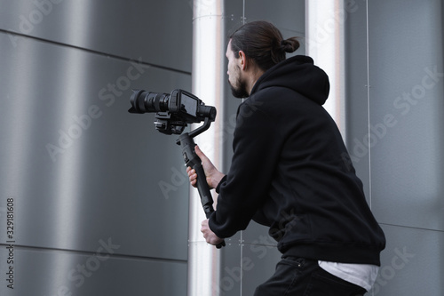 Photo Young Professional videographer holding professional camera on 3-axis gimbal stabilizer