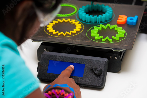 Photo Young 3d printing student using her finger on blank touch screen of a 3d printer , PLA plastic shapes on the print bed include skirts for first layer adhesion and multi color filament