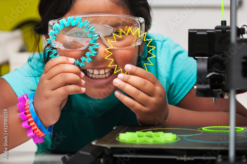 Photo Happy STEM student smiles and shows off the colorful 3d printed shapes, plastic parts on the print bed with skirt for plate adhesion