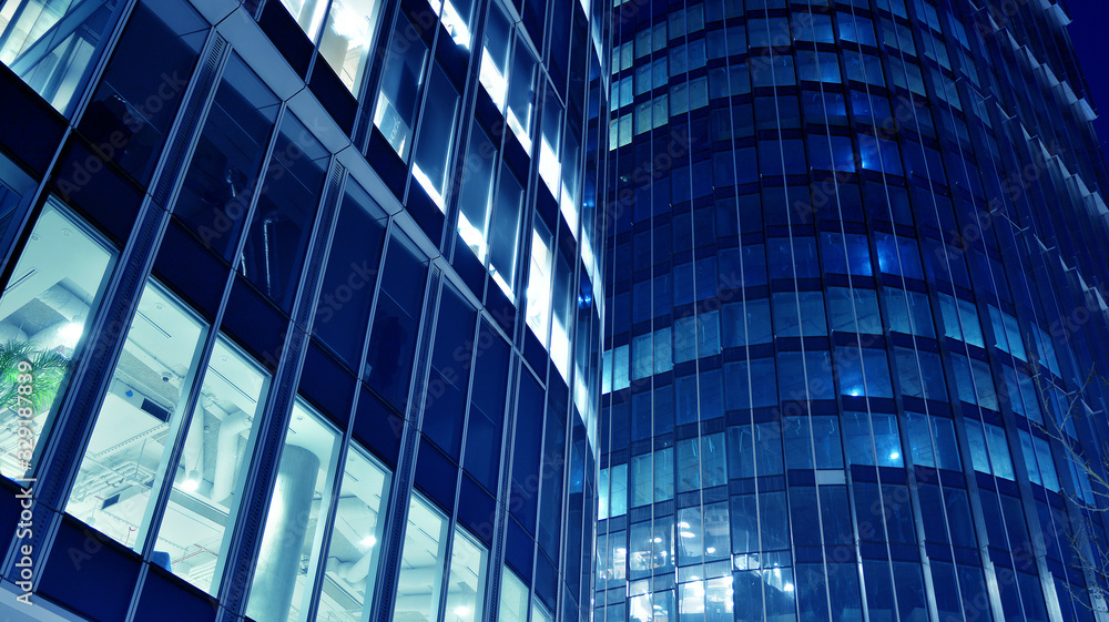 Fototapeta Night architecture - building with glass facade.Blue color of night lights. Modern building in  business district. Concept of economics, financial. Photo of commercial office building exterior. Abstra