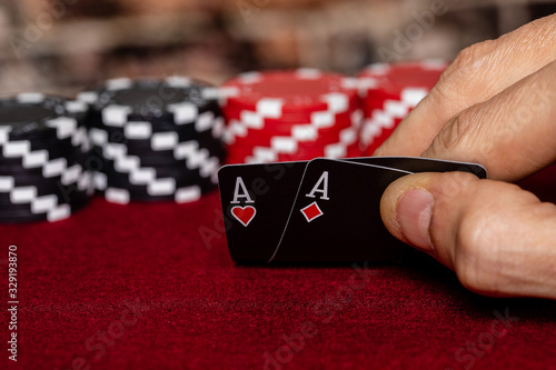 Photo a male caucasian hand Showing a Pair of Aces in the hole, Hearts and Diamonds, on a unique deck of black faced cards with Red and Black clay poker chips in the background
