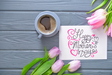 Beautiful Greeting Card With Flowers For Mother's Day And Cup Of Coffee On Wooden Background