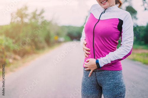 Young fitness woman suffering from stomach pain, during running in Forest mounta Canvas Print