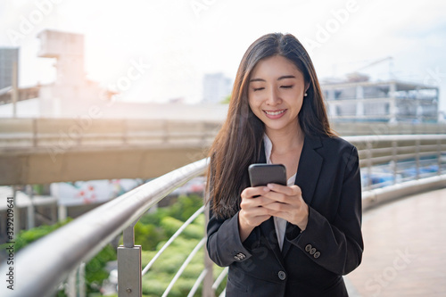 Obraz asian business woman holding a smartphone with two hands messaging and smiling, on top of a bridge platform standing next to railing guard with the city buildings and construction in the background. - fototapety do salonu