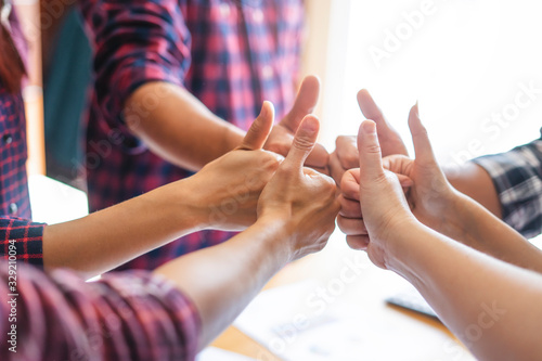 top view of employees standing around in a circle with their thumbs up and fists against each other, representing teamwork, positivity, community, help and support within small businesses or company Fototapet