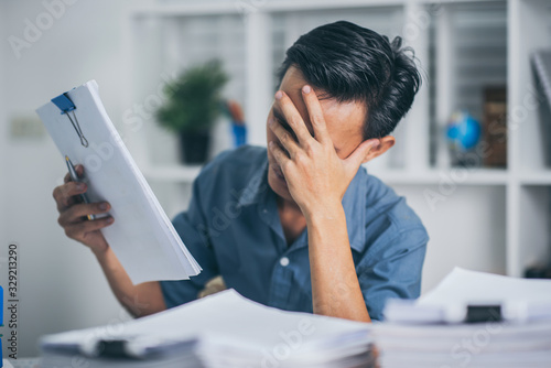 Fototapety, obrazy: Young business man doing financial reports feeling stress with stack of papers.