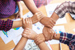 Leinwanddruck Bild - top view of employees standing around in a circle with their hand on each other's wrist to make a hexagon shape, representing teamwork community help and support within small businesses or company