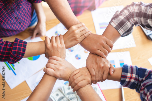 top view of employees standing around in a circle with their hand on each other's wrist to make a hexagon shape, representing teamwork community help and support within small businesses or company