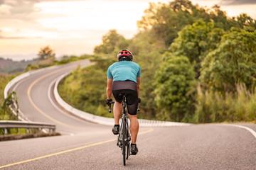 pogled straga na biciklista na vrhu zavojite ceste planine, vozi se crnim biciklom niz brdo, nosi biciklističku kacigu i plavi biciklistički dres, sa sivim oblacima zalaskom neba i šume u pozadini.