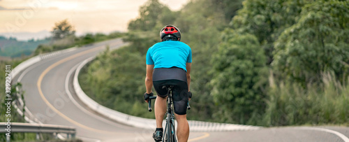 Fotografie, Obraz back view of a cyclist on top of a mountains winding road, riding a black bicycl