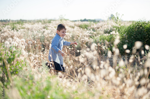 Fotografiet happy smiling small delightful kid running among dry and green grass in summer f