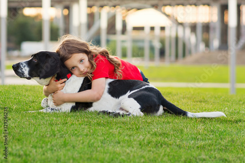 Fotografering Beautiful young girl is hugging her pet