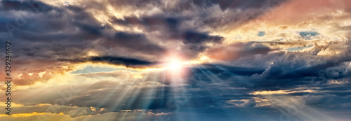 Fototapeta dramatic sunset sky landscape background natural color of evening cloudscape panorama with setting sun rays coming through clouds ultra wide panoramic view obraz