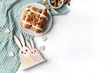 Delicious Vegan Homemade Hot Cross Buns On A Plate. The Plate Sits On A Sage Coloured Tea Towel And Is Surrounded By A Bowl Of Various Nuts, Wooden Hearts And Wooden Easter Bunny Decorations.