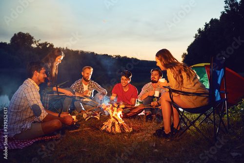 Obraz Friends are laughing sitting by the fire next to the tent. - fototapety do salonu