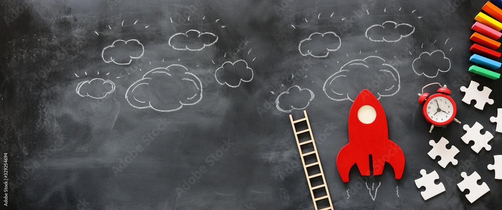 Fototapeta education or innovation concept. Wooden rocket over blackboard background. top view