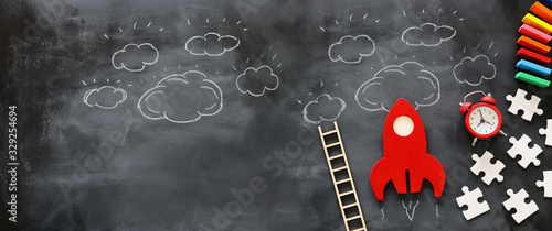 education or innovation concept. Wooden rocket over blackboard background. top view