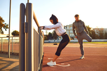 Couple in sportswear doing warm-up at the stadium