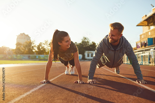 Fotografía Young couple doing pushups in the stadium