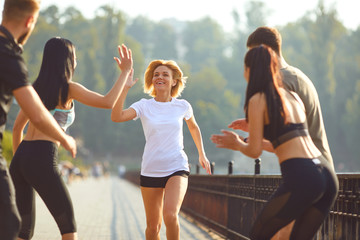 Girl runner runs fun with a group of friends in a park