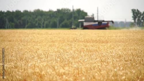 Aufkleber - Blurred сombine harvester for harvesting wheat. Slow motion