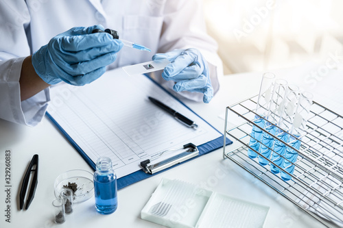 Cuadros en Lienzo Scientist or medical in lab coat holding test tube with reagent, mixing reagents