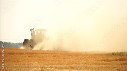 Aufkleber - A tractor with a plow plows the field after harvesting. Slow motion