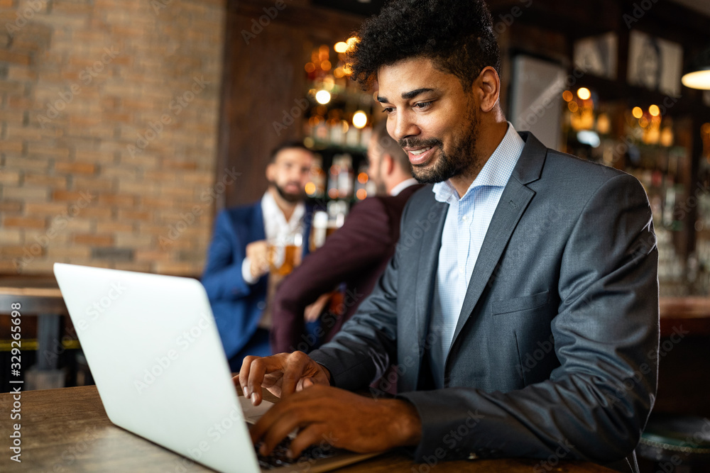 Fototapeta Handsome young business man, blogger or remote working with laptop in bar