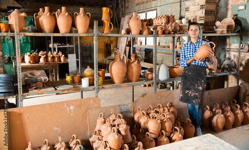 Woman chooses pots clay pots in store warehouse Wallpaper Mural
