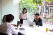A team of Asian business owners are teaching job for new people using computers. New employees are being trained by business owners.