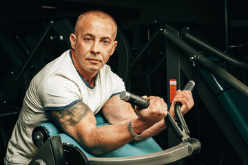 Senior man doing exercises for arms in a training machine in gym