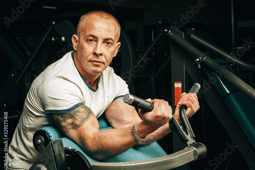 obraz PCV Senior man doing exercises for arms in a training machine in gym